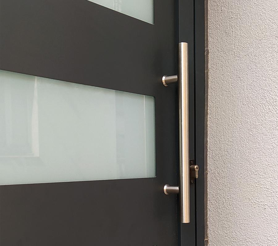 porta d'entrada amb barra d'acer inoxidable i vidres glaçats