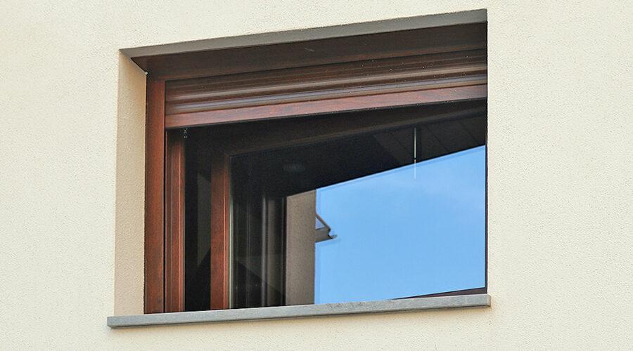 Finestra de PVC practicable i abatible acabats en nogal, amb persiana motoritzada